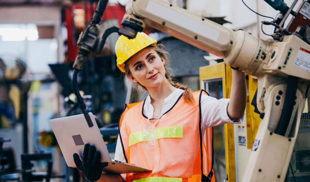 a feminine presenting person holding a laptop whilst inspecting the arm of a machine